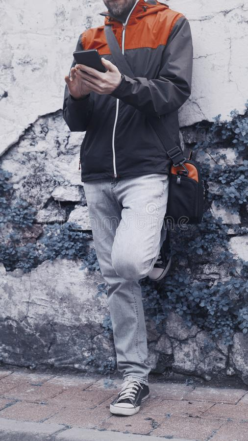 Condizione del giovane contro un fondo della parete e uno smartphone usando fotografie stock libere da diritti