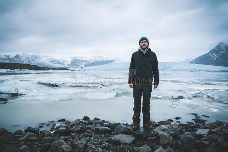 Condizione del giovane davanti alla laguna dell'iceberg di Fjallsarlon all'estremità del sud del ghiacciaio Vatnajokull, con il g immagini stock