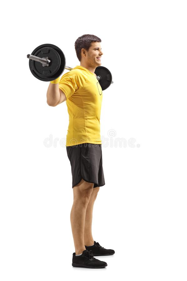 Condizione del giovane e pesi di sollevamento sulle spalle immagine stock