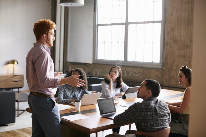 Condizione del giovane per parlare ai colleghi ad una riunione del lavoro immagini stock libere da diritti