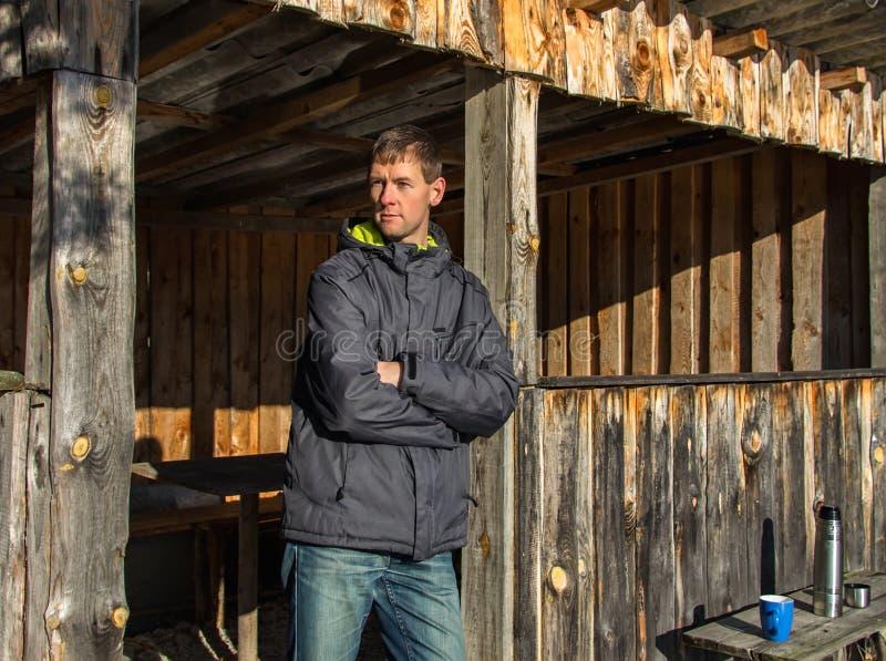 Condizione del giovane del ritratto nella costruzione di legno con il termos e la tazza blu fotografia stock