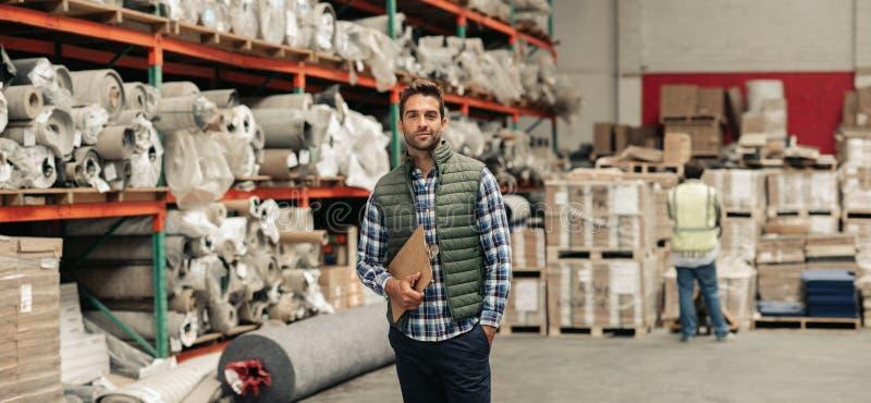 Condizione del lavoratore con una lavagna per appunti di inventario su un pavimento del magazzino immagine stock libera da diritti