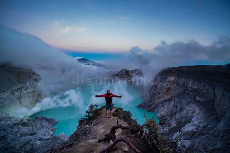 Condizione del viaggiatore dell'uomo sul bordo del vulcano di Ijen del cratere con il cielo variopinto alla mattina immagini stock