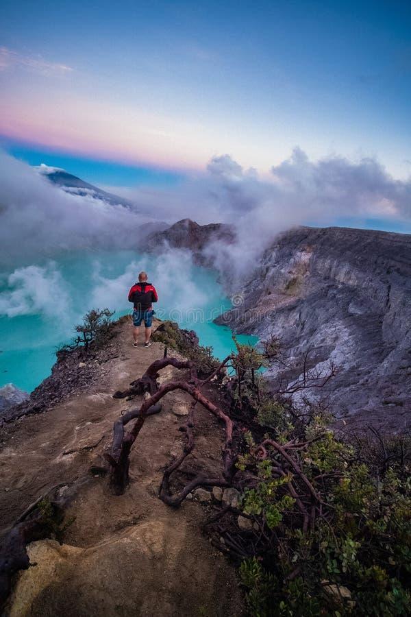 Condizione del viaggiatore dell'uomo sul bordo del vulcano di Ijen del cratere con il cielo variopinto alla mattina fotografia stock