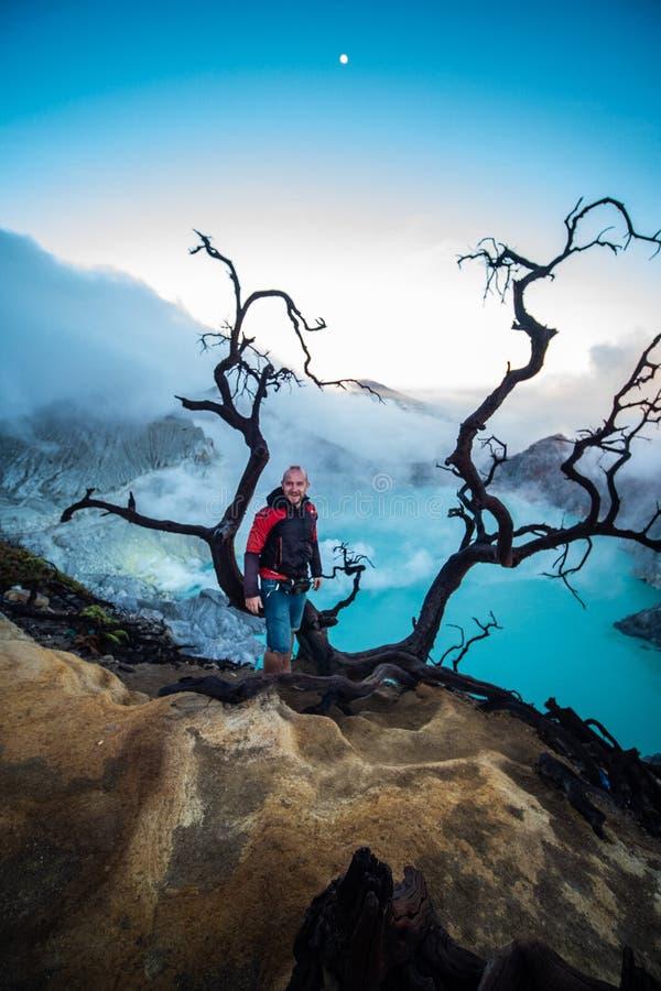Condizione del viaggiatore dell'uomo vicino all'albero morto sul bordo del vulcano di Ijen del cratere con il cielo variopinto al fotografie stock