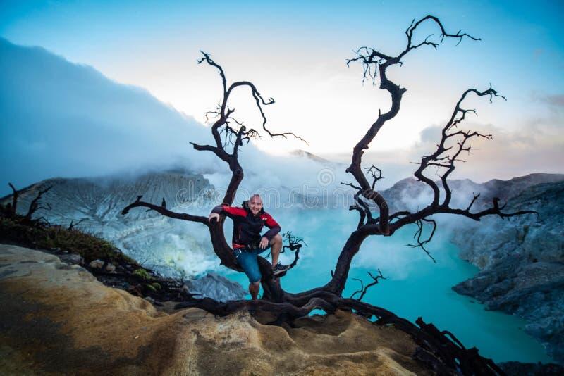 Condizione del viaggiatore dell'uomo vicino all'albero morto sul bordo del vulcano di Ijen del cratere con il cielo variopinto al immagine stock libera da diritti