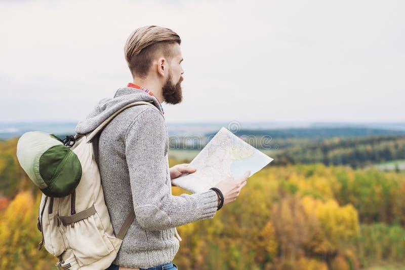 Condizione del viaggiatore del giovane sopra la collina e guardare alla mappa concetto di corsa fotografie stock
