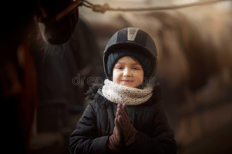 Condizione dell'adolescente con il cavallo in una stalla fotografie stock