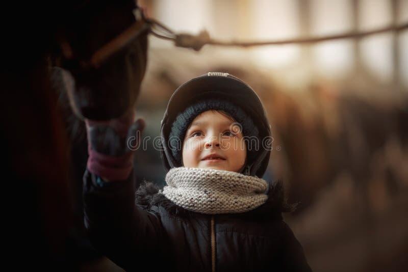 Condizione dell'adolescente con il cavallo in una stalla fotografia stock libera da diritti