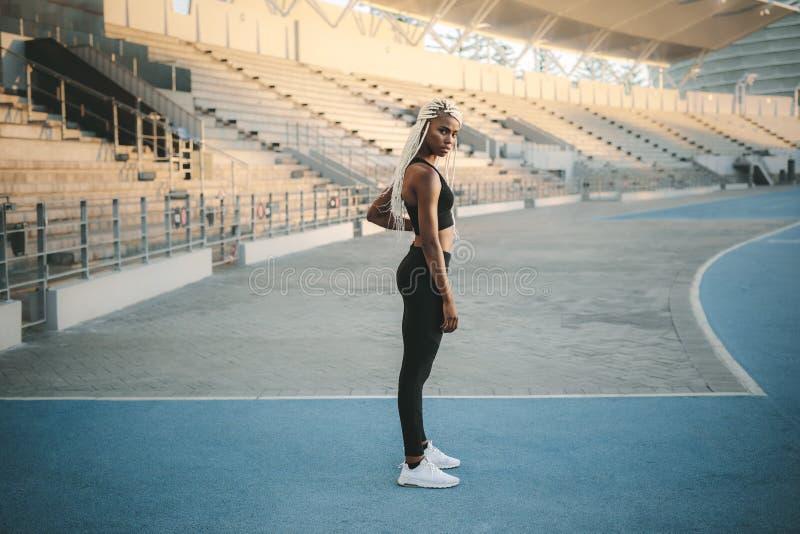 Condizione dell'atleta vicino ai supporti in uno stadio immagine stock