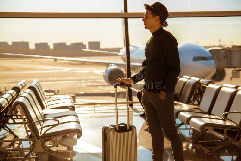 Condizione dell'uomo con i suoi bagagli ad un aeroporto immagine stock libera da diritti