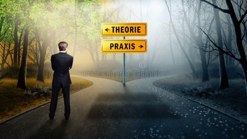 """Condizione dell'uomo d'affari ad una strada trasversale con i segnali stradali """"teoria """"e """"praxis """"in tedesco immagine stock"""