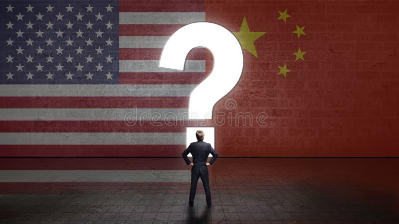 Condizione dell'uomo d'affari davanti ad una parete con un questionmark ed alle bandiere degli S.U.A. e della porcellana fotografie stock libere da diritti