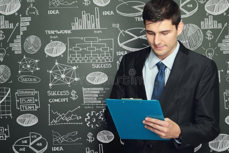Condizione dell'uomo d'affari mentre leggendo rapporto fotografia stock libera da diritti