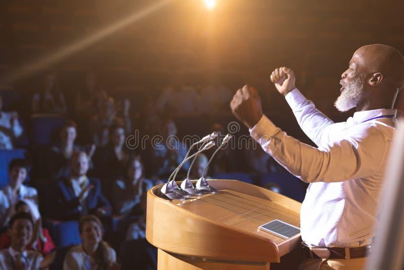 Condizione dell'uomo d'affari vicino al podio ed al discorso dare al pubblico nella sala fotografie stock