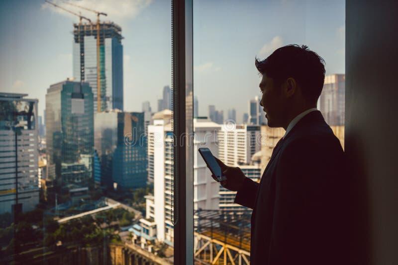 Condizione dell'uomo d'affari vicino alla finestra facendo uso del cellulare fotografie stock libere da diritti