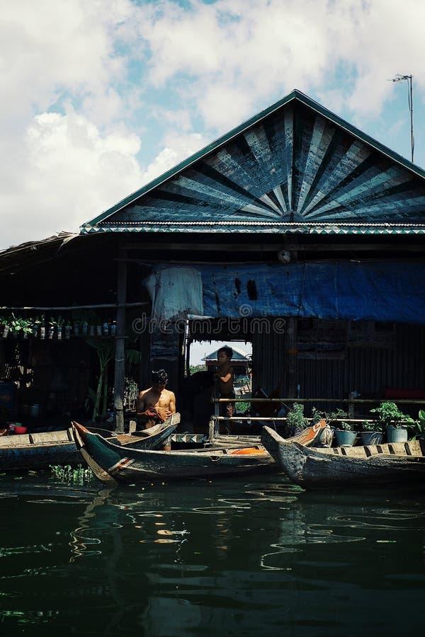 condizione dell'uomo davanti alla sua casa ad uno stabilimento illegale sviluppata sui trampoli in mezzo al lago sommerso immagine stock
