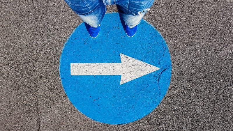 Condizione dell'uomo sul giusto simbolo del segnale stradale di traffico di giro con la freccia bianca che indica destra fotografie stock