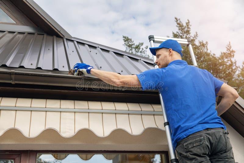 Condizione dell'uomo sulla scala e sulla grondaia di pulizia della pioggia del tetto fotografie stock