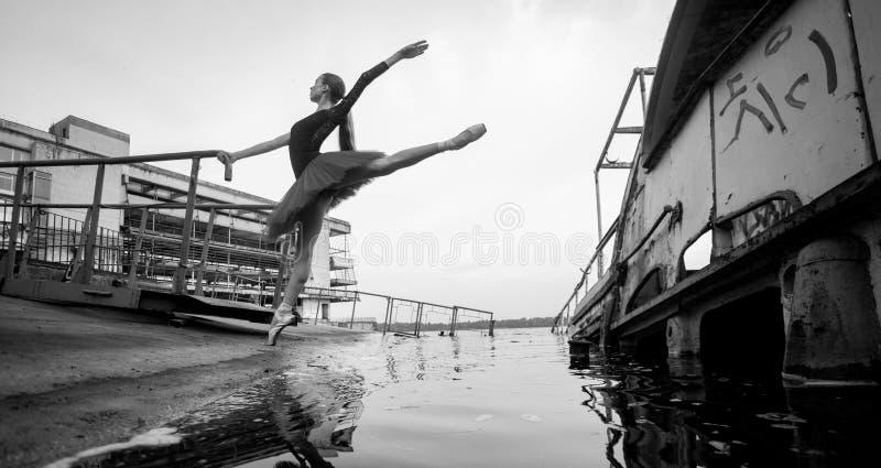 Condizione della ballerina nella posa di arabesque sui precedenti del fiume, del pilastro e di vecchia barca immagine stock