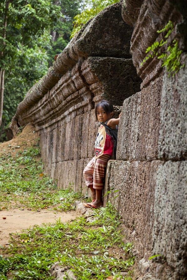Condizione della bambina contro una vecchia parete di pietra fotografia stock libera da diritti