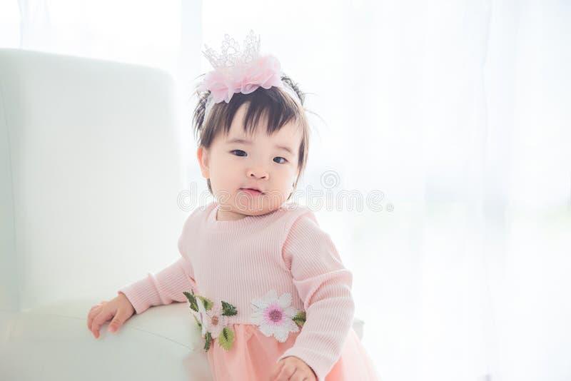 Condizione della bambina davanti alla finestra luminosa immagini stock