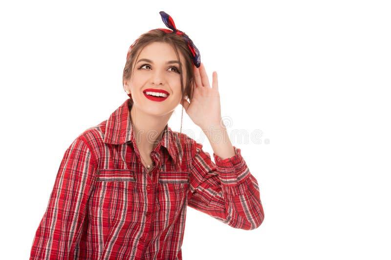 Condizione della donna con la sua mano dietro il suo orecchio e uno sguardo di anticipazione come aspetta per sentire un framment immagini stock