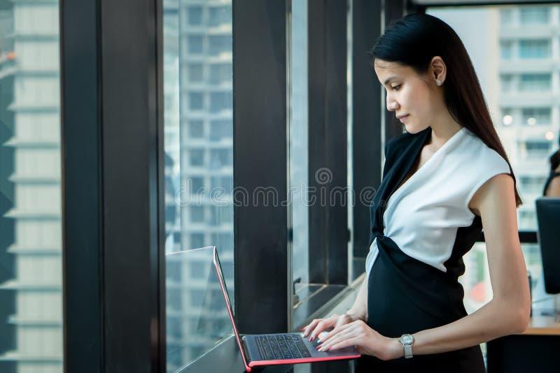 Condizione della donna dell'ufficio vicino alla finestra ed al computer portatile usando in ufficio immagine stock libera da diritti
