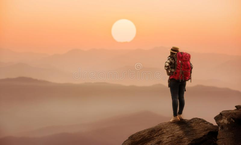 Condizione della donna dello zaino sulla collina con la bella natura immagini stock