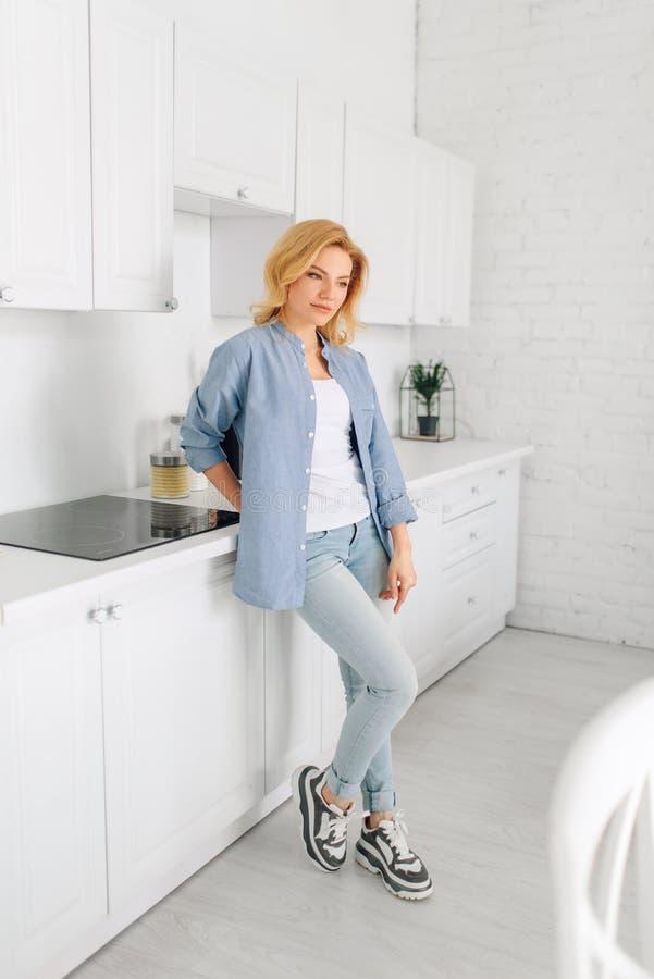 Condizione della donna sulla cucina con l'interno bianco come la neve immagine stock libera da diritti