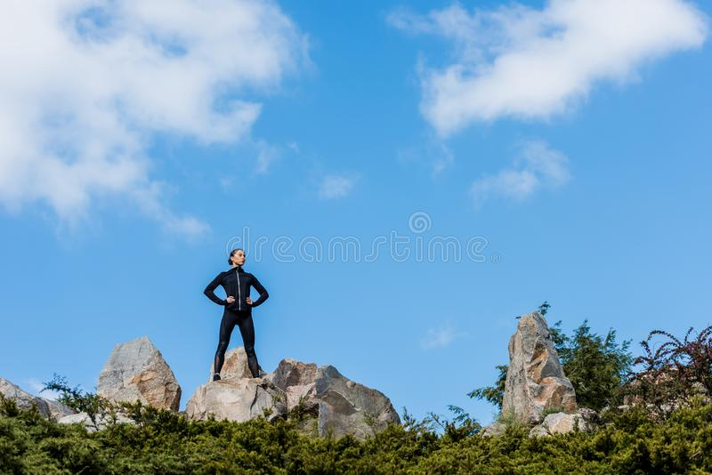 condizione della donna sulle rocce con le armi akimbo fotografia stock