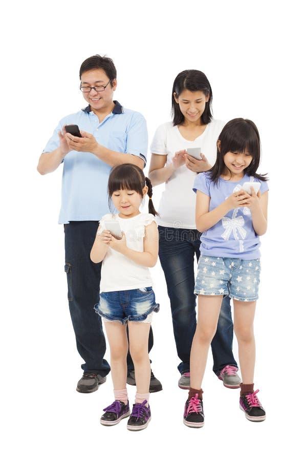 Condizione della famiglia ed usando Smart Phone felici insieme fotografie stock libere da diritti