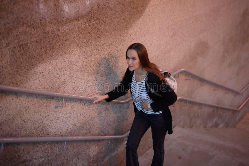 Condizione della giovane donna e le scale del sottopassaggio, tenuta il suo stomaco fotografia stock libera da diritti