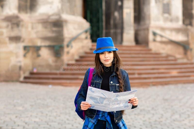 Condizione della giovane donna vicino alla chiesa in vecchia città Leopoli e nelle tenute una mappa a disposizione l'ucraina fotografia stock