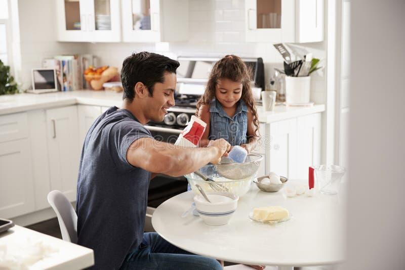 Condizione della ragazza al tavolo da cucina che prepara la miscela del dolce con suo padre, visto dalla entrata fotografia stock libera da diritti