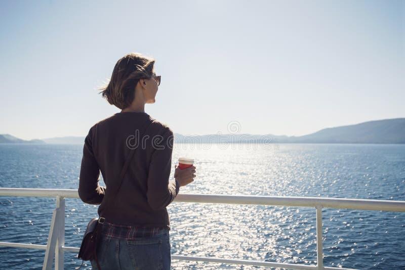 Condizione della ragazza del viaggiatore sul traghetto, esaminante il mare e tenente una tazza di caffè, un viaggio e un concetto immagine stock libera da diritti