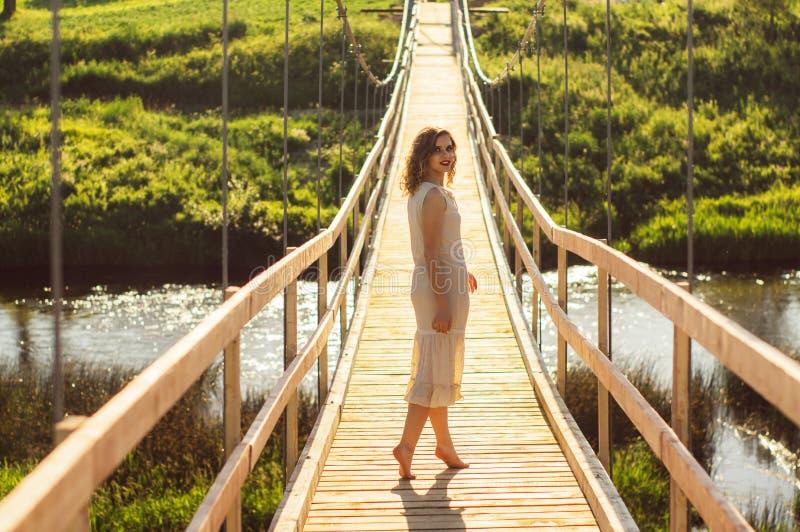 Condizione della ragazza sul centro del ponte di legno attraverso il fiume fotografia stock