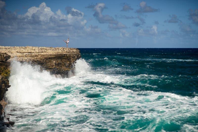 Condizione della ragazza sull'orlo della baia del ponte del diavolo - Antigua e Barbuda marino tropicale caraibico Concetto di li immagini stock libere da diritti