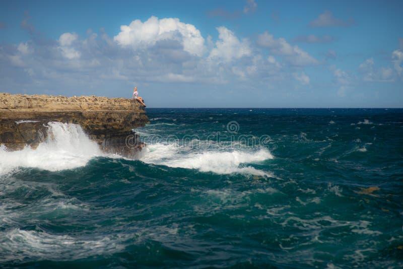 Condizione della ragazza sull'orlo della baia del ponte del diavolo - Antigua e Barbuda marino tropicale caraibico Concetto di li fotografia stock
