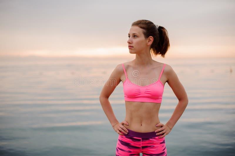 Condizione della ragazza sulla spiaggia ed esaminare la distanza immagini stock