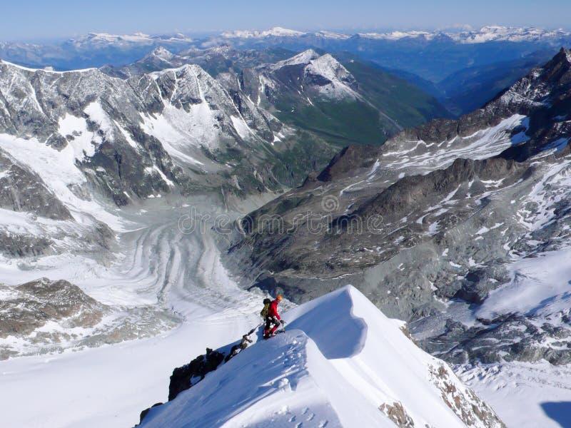 Condizione dello scalatore di montagna alta su su una cresta nevosa stretta ed esposta della montagna sotto un cielo blu con le p immagine stock