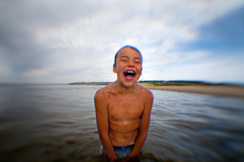 Condizione di grido piacevole ed allegra del ragazzo nell'acqua fotografia stock