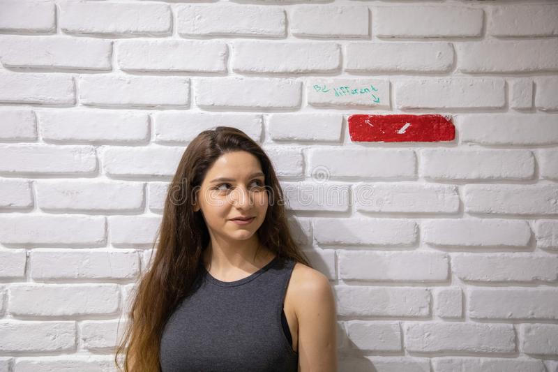 Condizione di modello femminile attraente vicino ad un muro di mattoni bianco con un singolo mattone rosso immagine stock