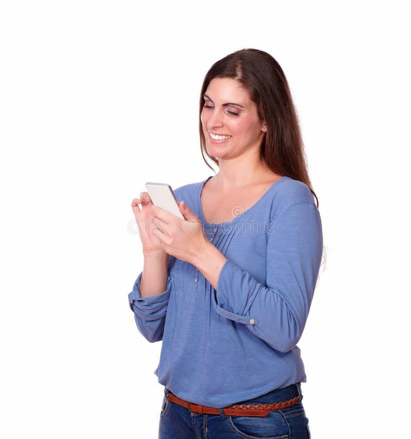 Condizione e mandare un sms carismatici della giovane signora fotografia stock libera da diritti