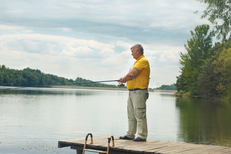 Condizione e pesca dell'uomo senior sul bacino fotografie stock