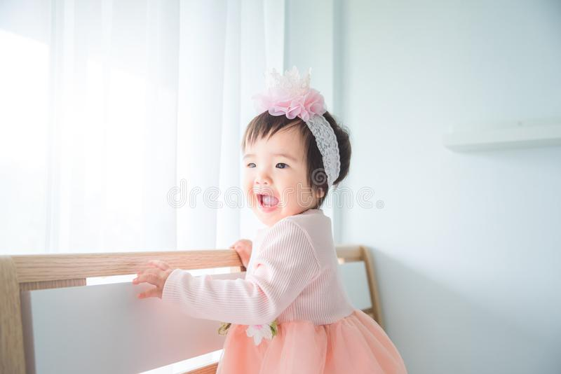 Condizione e sorrisi della bambina sul letto in camera da letto immagini stock libere da diritti