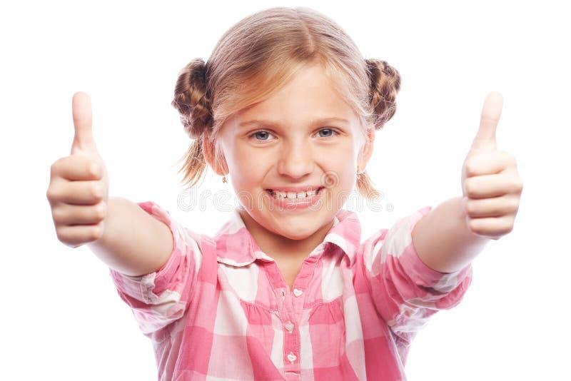 Condizione felice del bambino della bambina isolata sopra fondo bianco Guardando macchina fotografica che mostra i pollici su fotografia stock