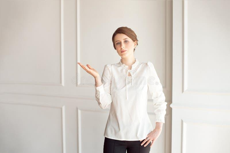 Condizione felice della giovane donna vicino ad una parete bianca Mano che mostra un posto per indicare copyspace fotografia stock