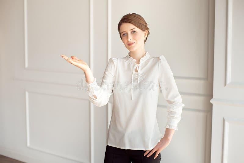Condizione felice della giovane donna vicino ad una parete bianca Mano che mostra un posto per indicare copyspace immagini stock