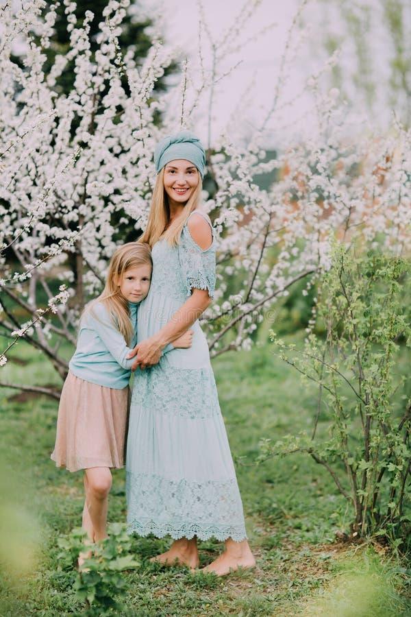 Condizione felice della mamma con la figlia su un parco della ciliegia della molla fotografia stock